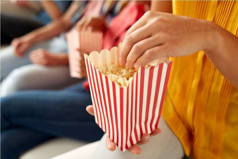 close-up-of-happy-friends-eating-popcorn-at-home