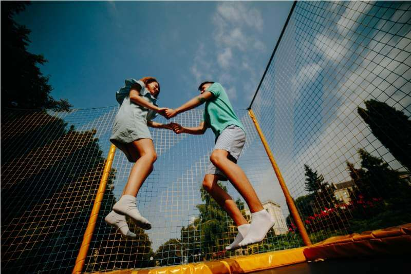 couple-jumping-on-trampoline-in-the-park