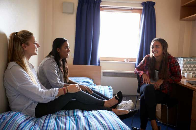 female-students-relaxing-in-bedroom-of-campus