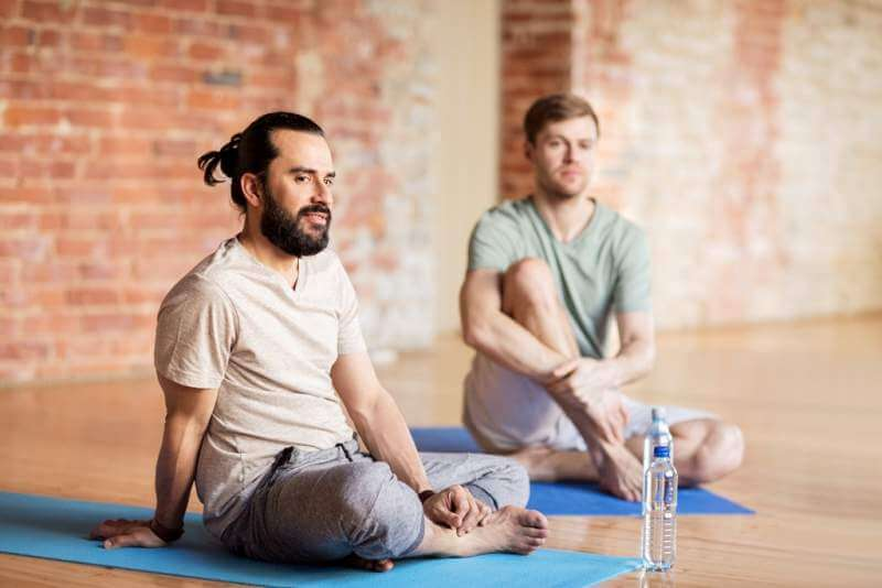 men-resting-on-mats-at-yoga-studio