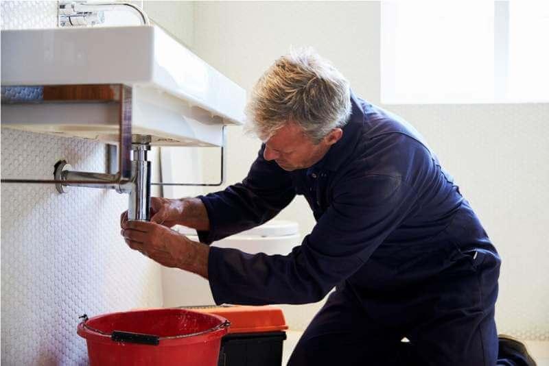 plumber-working-on-sink-in-bathroom
