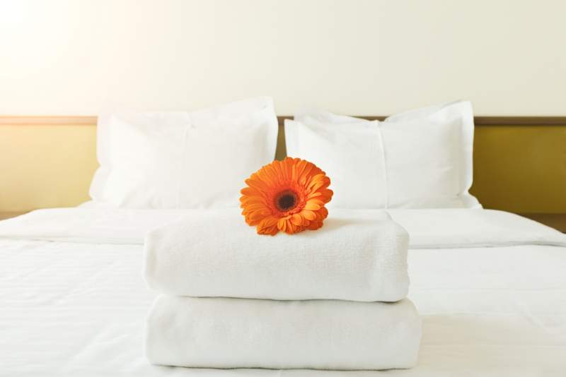 stack-of-towels-and-flower-on-bed-in-hotel-room
