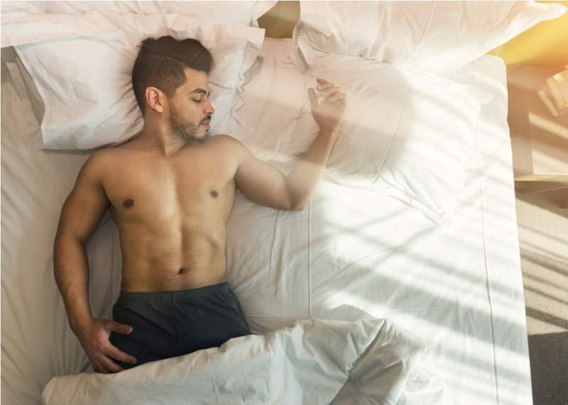 top-view-of-shirtless-young-man-sleeping-in-bed