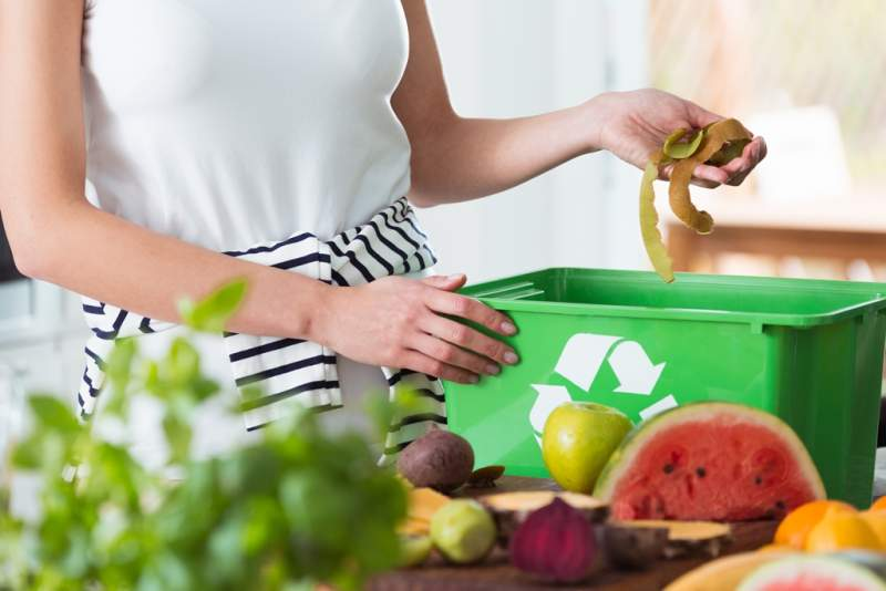 woman-composting-organic-kitchen-waste