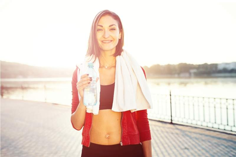 woman-holding-bottle-of-water-and-a-towel