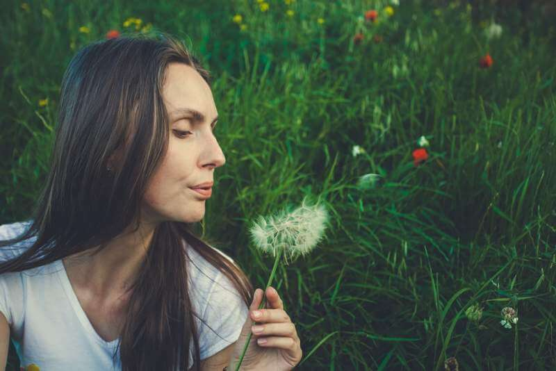 allergy-free-concept-woman-blowing-dandelion