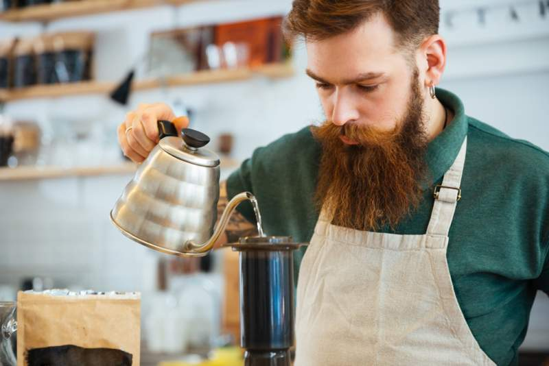 barista-pouring-water-on-coffee-ground