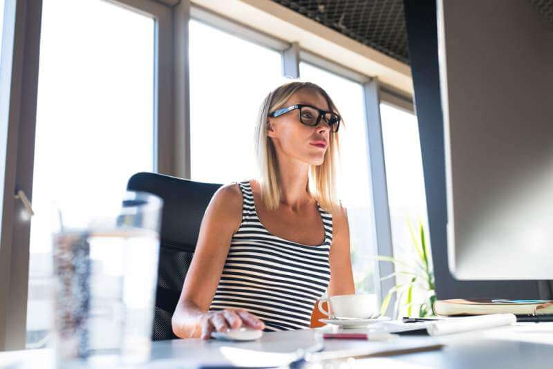 businesswoman-with-computer-in-her-office-working
