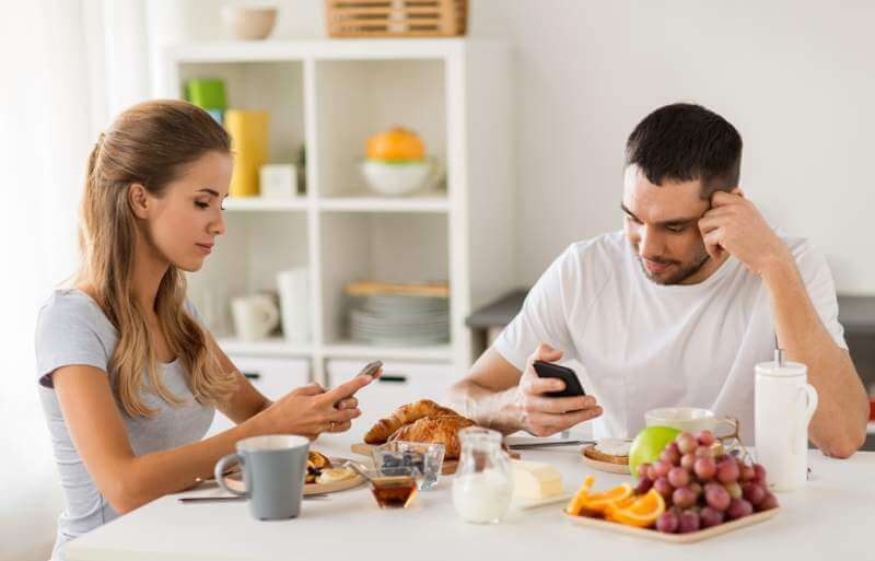 couple-with-smartphones-having-breakfast-at-home