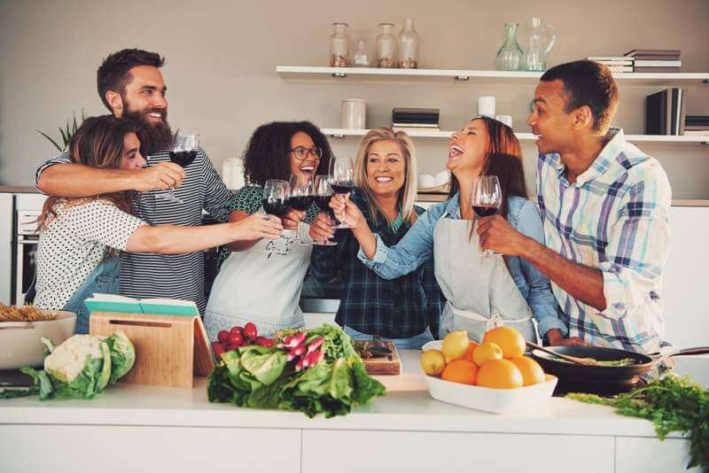 fun-group-toasting-wine-glasses-while-cooking