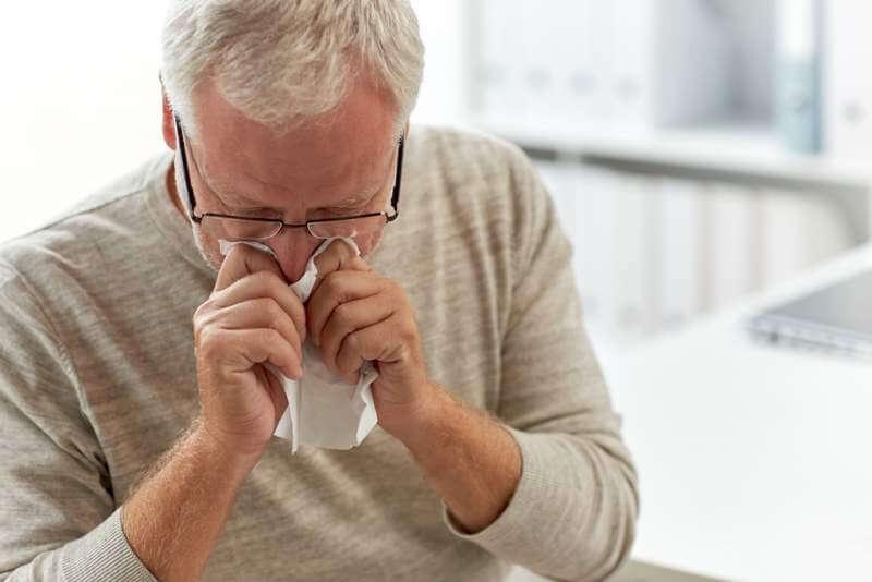 senior-man-blowing-nose-with-napkin-at-hospital