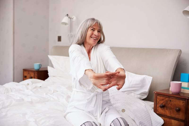 senior-woman-waking-up-and-stretching-in-bedroom