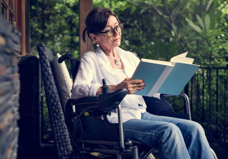 woman-reading-a-book-in-a-wheelchair