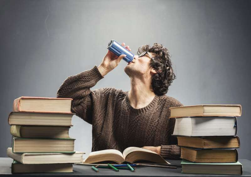 young-man-studying-and-drinking-energy-drink
