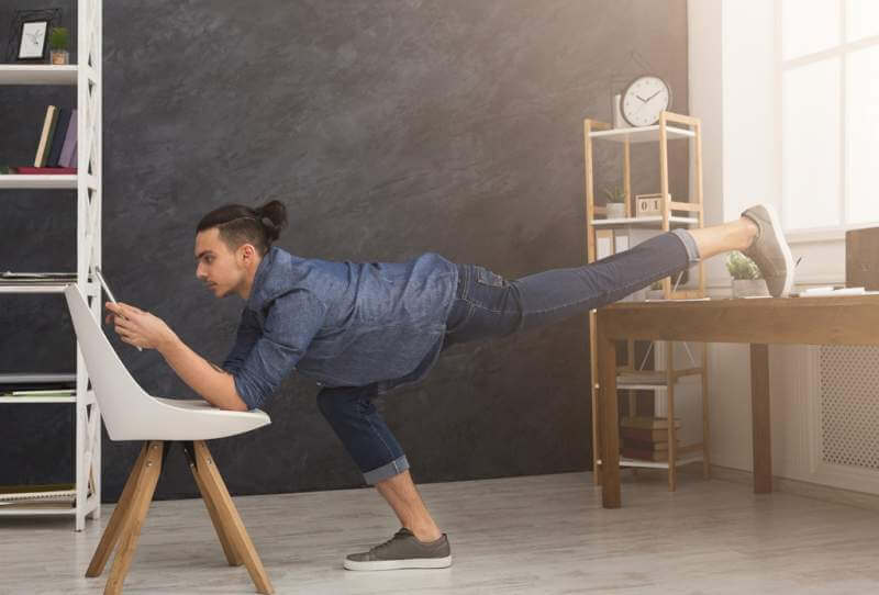 flexible-man-practicing-yoga-at-workplace