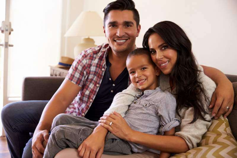 portrait-of-happy-family-sitting-on-sofa