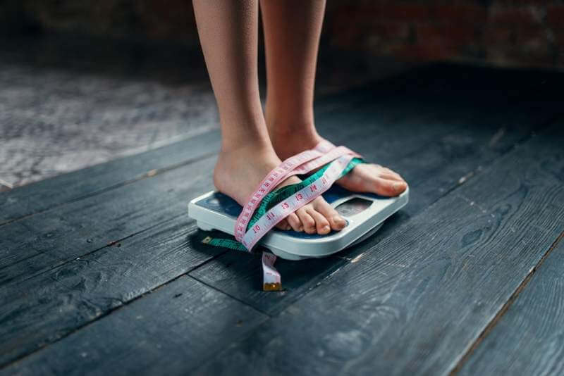 womans-feet-on-the-scales-tied-with-measuring