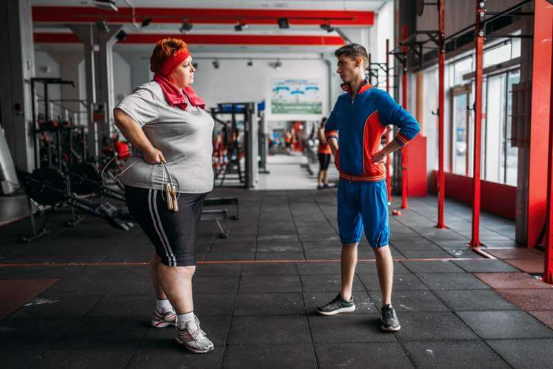 fat-woman-talks-with-instructor-after-exercise
