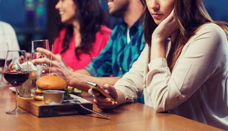 woman-with-smartphone-and-friends-at-restaurant