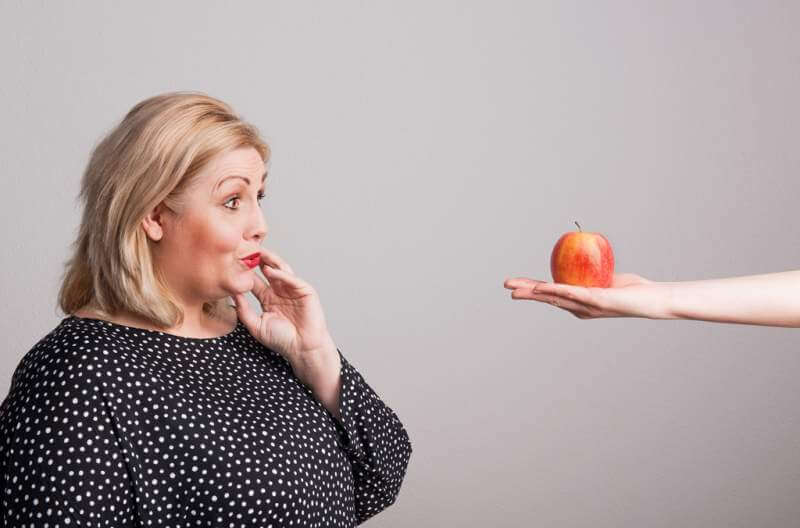 a-female-hand-giving-an-apple-to-an-attractive