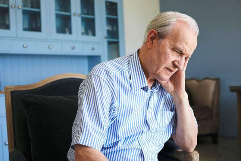 senior-man-sitting-in-chair-at-home-suffering