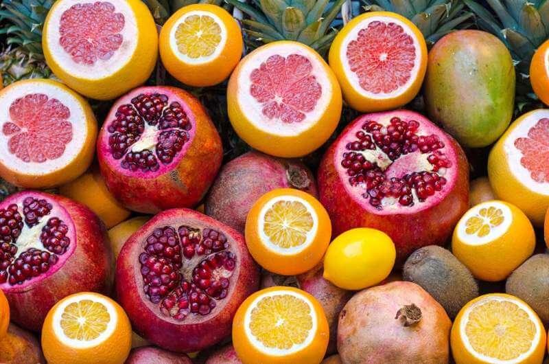 Orange Fruit Beside Lemon and Red Round Fruit during Daytime