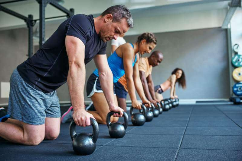 focused-people-doing-pushups-on-weights-in-a-gym