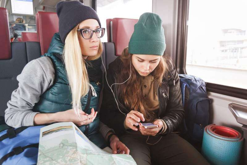 two-young-women-travelers-with-backpacks-and-map