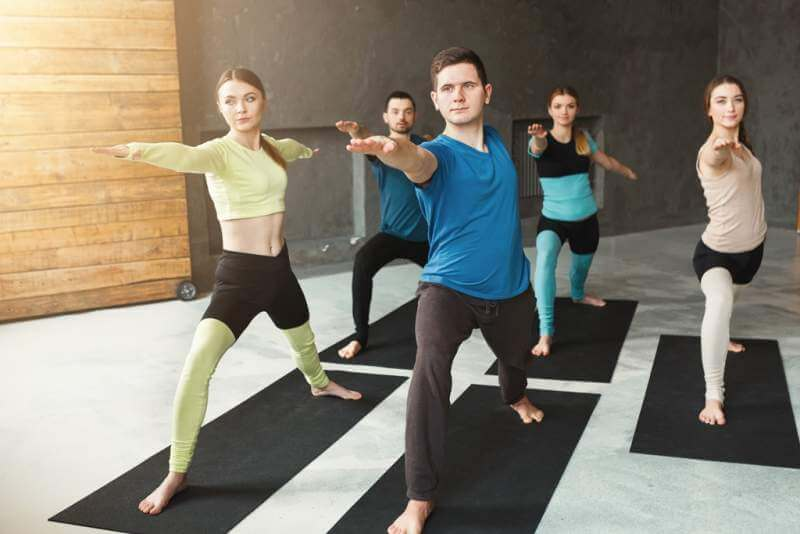 young-women-and-men-in-yoga-class-doing