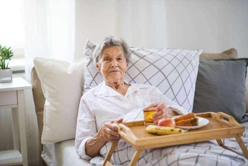 a-sick-senior-woman-with-food-on-a-wooden-tray