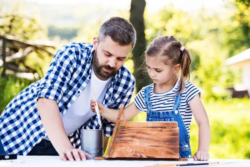 father-with-a-small-daughter-outside-making