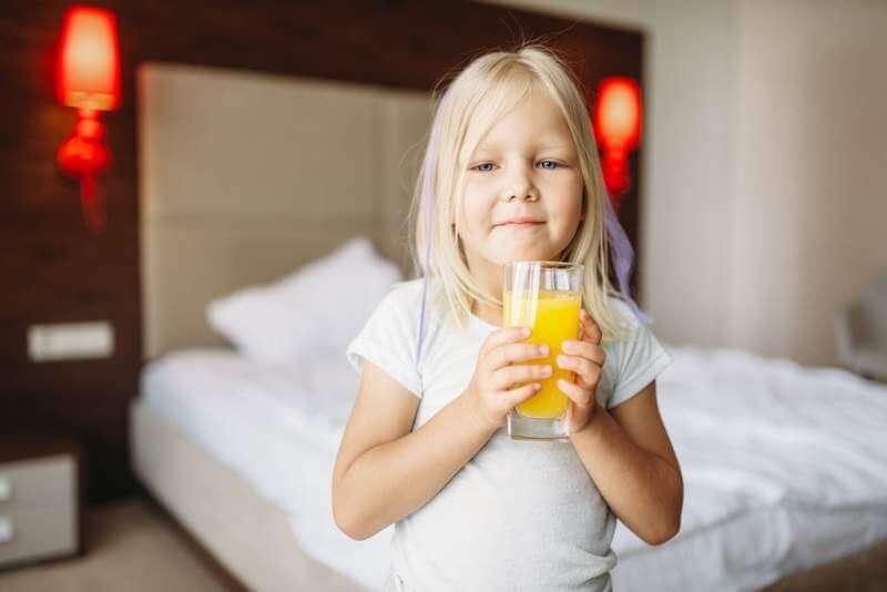 little-girl-with-glass-of-orange-juice-in-bedroom