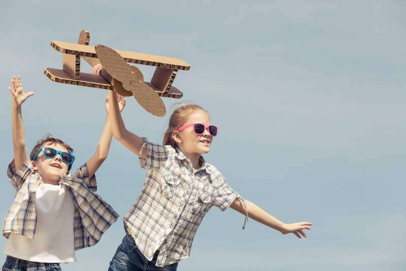 little-kids-playing-with-cardboard-toy-airplane