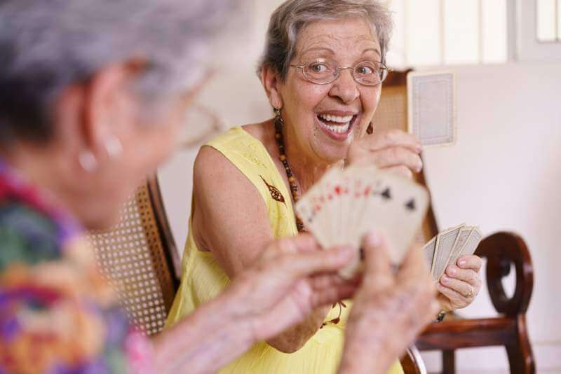 old-women-enjoy-playing-card-game-in-hospice