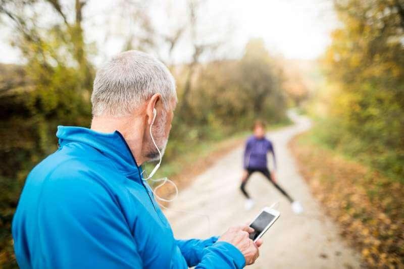 senior-runners-in-nature-stretching-man