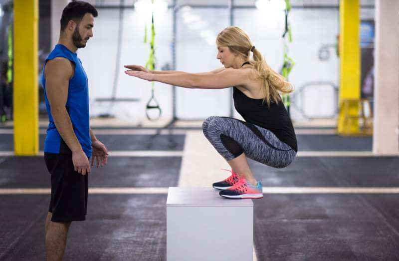 woman-working-out-with-personal-trainer-jumping