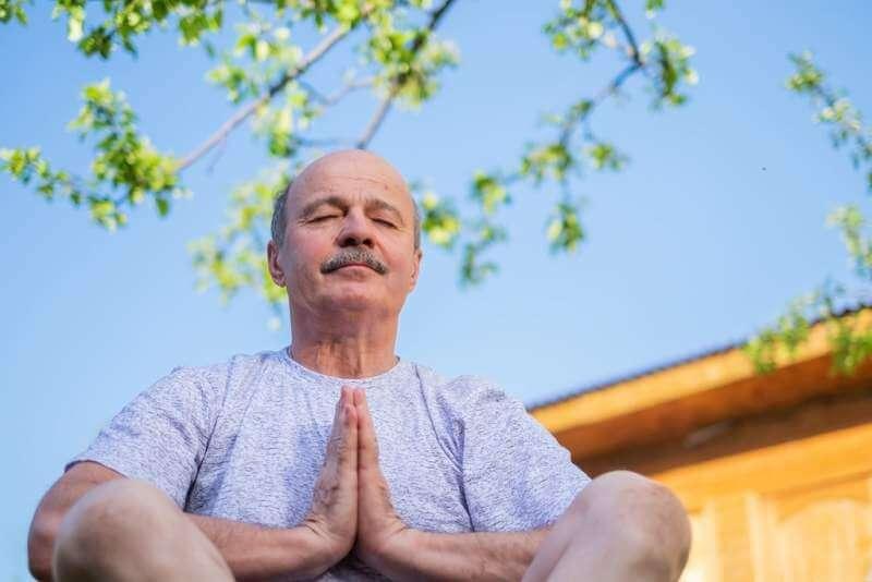 peaceful-senior-man-meditating-seated-ooutdoor