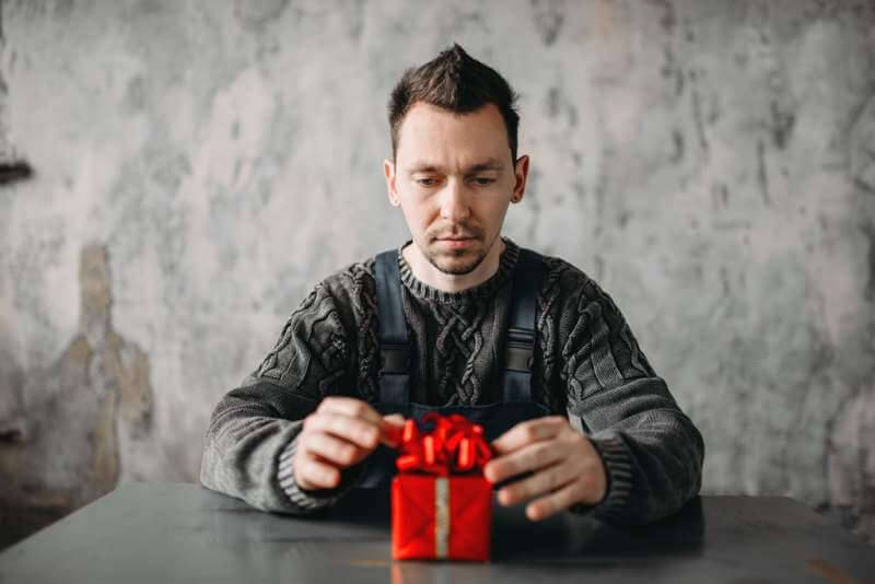 autist-man-sitting-against-gift-in-wrapping-paper