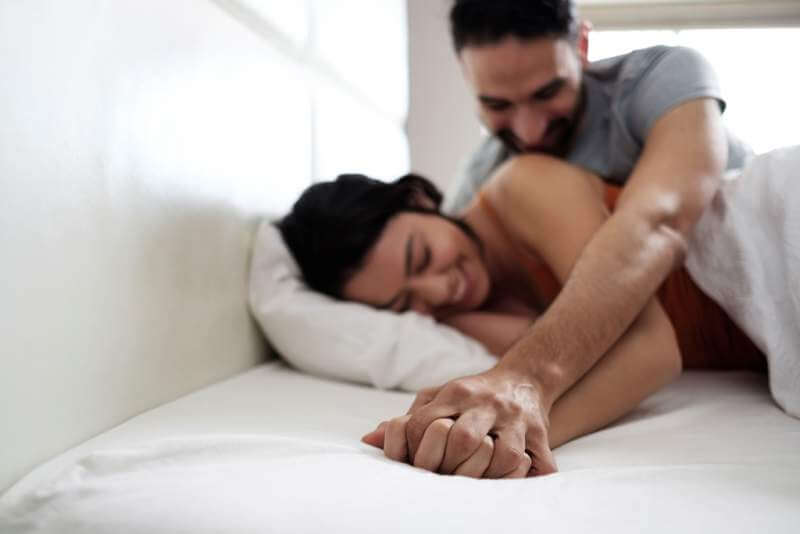 happy-latino-couple-holding-hands-in-home-bed