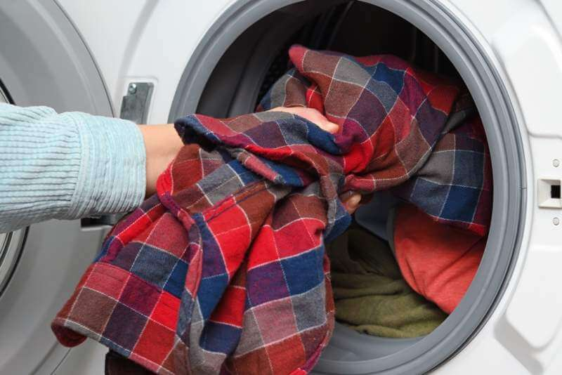 woman-puts-clothes-in-washing-machine
