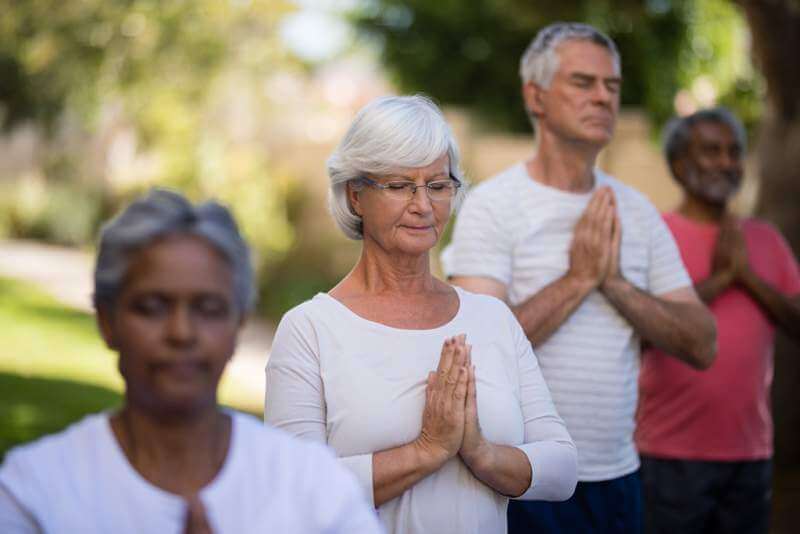 senior-people-meditating-in-prayer-position-while