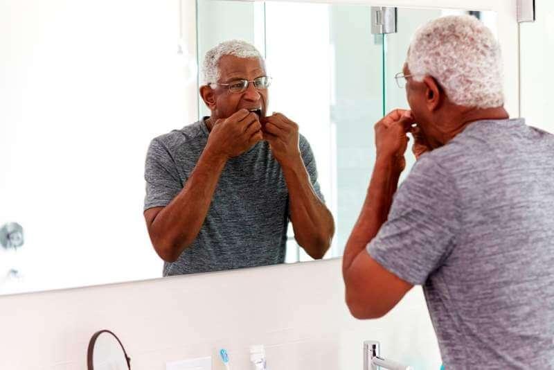 senior-man-flossing-teeth-looking-at-reflection