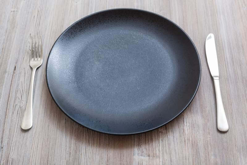black-plate-with-knife-spoon-on-gray-brown-table