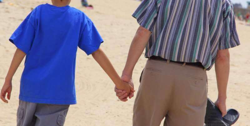 teen-holding-his-dad-s-hand-while-talking-walking